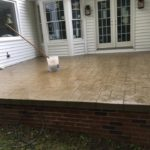 Stamped concrete porch on a brick masonry foundation.