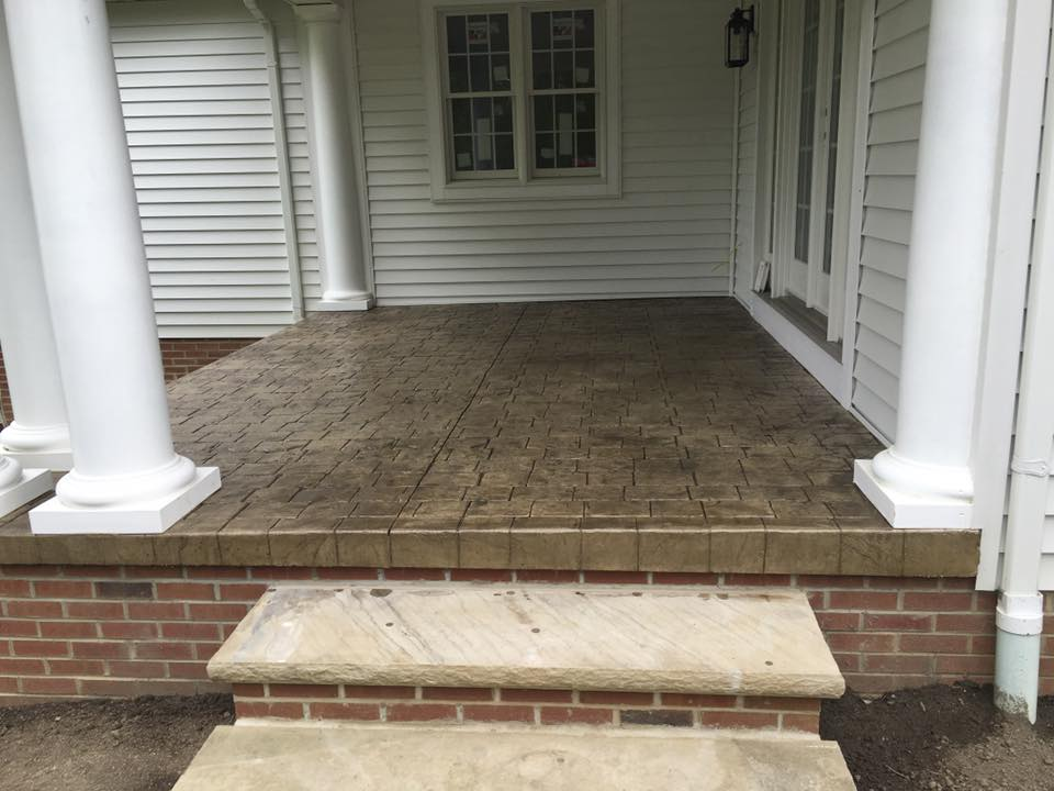 Stamped concrete porch with brick masonry steps.