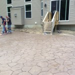 Placement of a stamped concrete with random stone pattern.