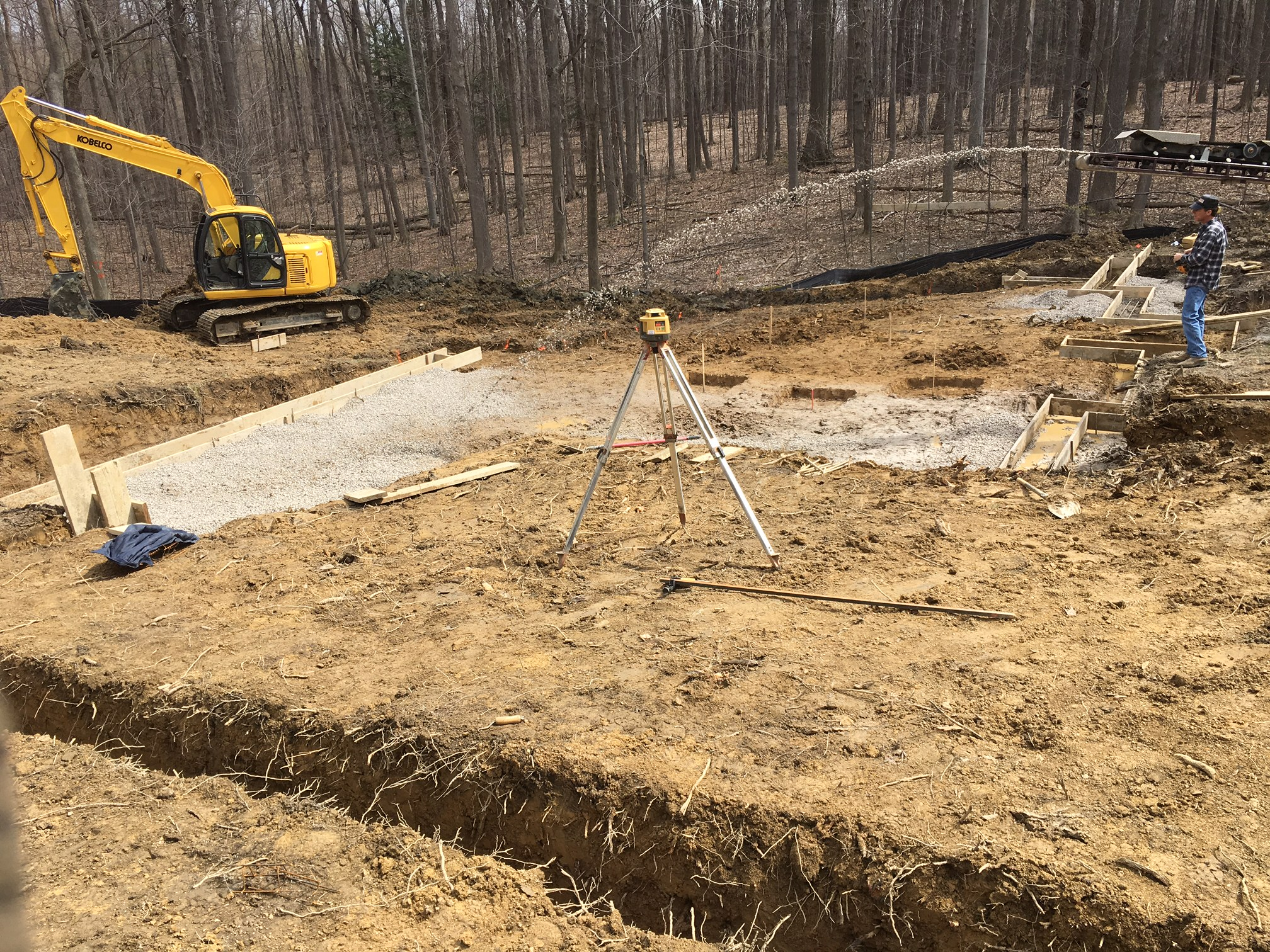 Placing stone for a new home masonry foundation